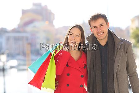 couple of shoppers walks in winter