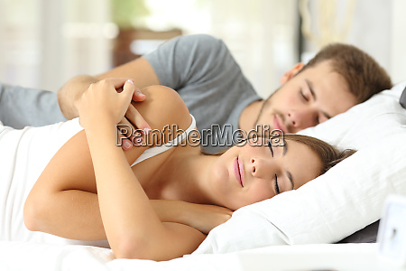 couple sleeping together at hotel or