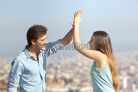 happy friends giving high five outdoors
