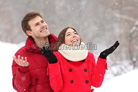 happy couple enjoying snow in winter