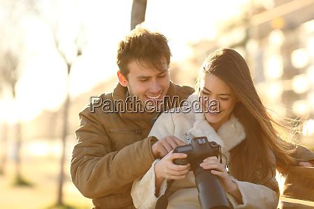 happy couple checking photos on a