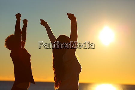 excited friends raising arms at sunset