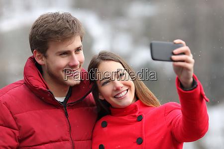 happy couple taking selfies in winter