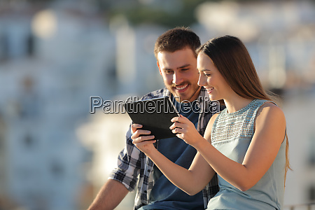 happy couple watching tablet content outside