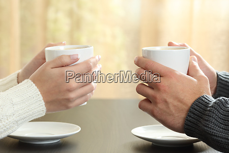 hands of couple with coffee cups