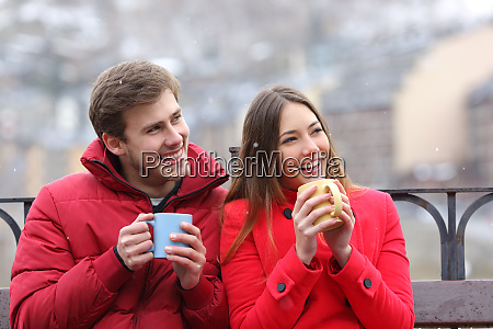 happy couple drinking hot drinks looking
