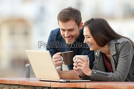 happy couple checking laptop content on
