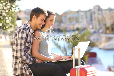 couple of tourists using a laptop