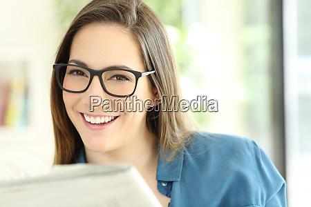 woman holding a newspaper wearing eyeglasses
