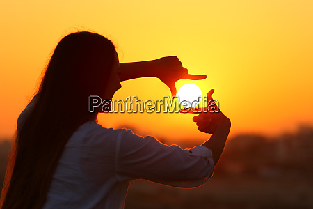 woman framing sun with fingers at