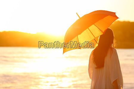 woman with umbrella at sunset on