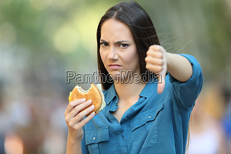 woman refusing a burger with thumbs