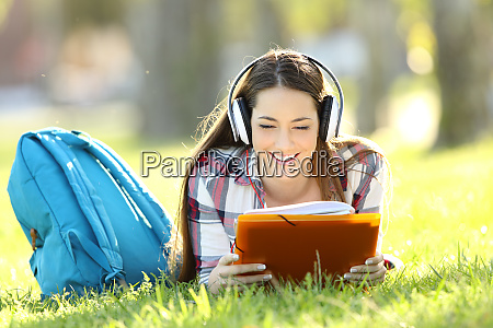 student reading notes and listening an