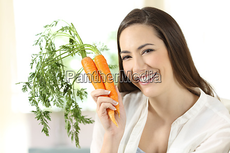 girl showing a bundle of carrots