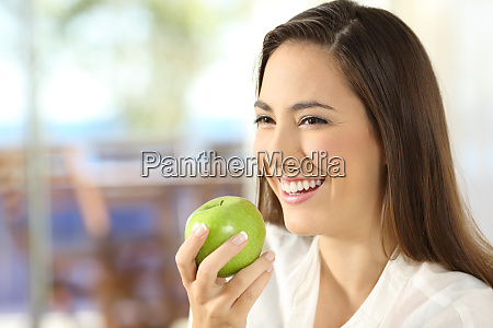 happy woman holding an apple looking