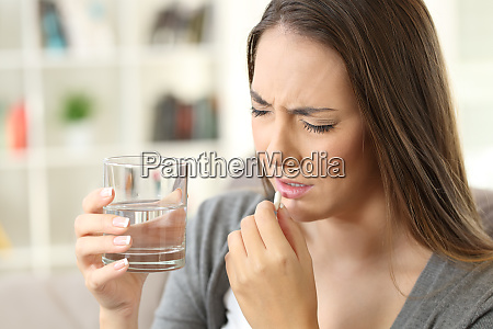painful woman taking a pill