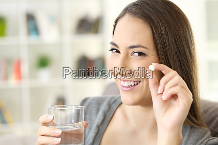 woman holding a pill looking at