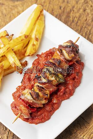 shashlik with french fries on wood