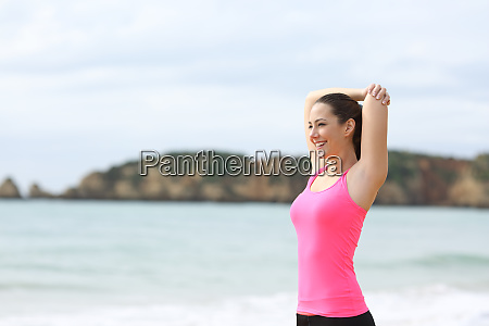 sportswoman stretching arms after sport