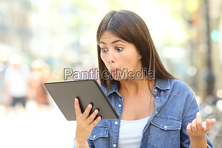 confused girl with a tablet outdoors
