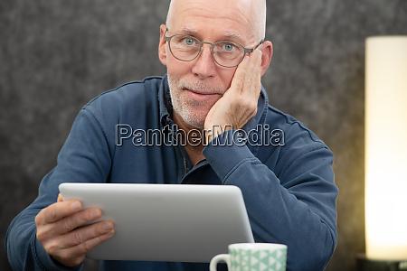 handsome senior man using tablet computer