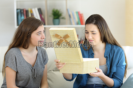 disappointed girl opening a gift beside