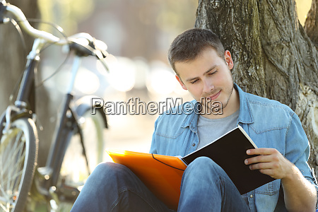 student studying reading notes outdoors