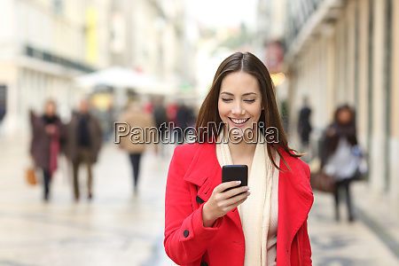 happy woman walking using a cellphone