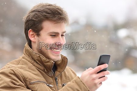happy man checking phone on winter