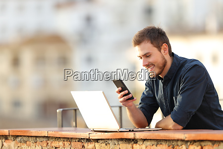 happy man using phone and laptop