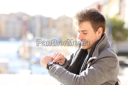 man checks smartwatch in a coffee