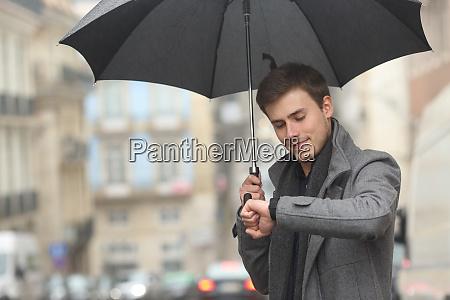 man checking smartwatch under the rain