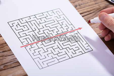 person solving maze puzzle with red