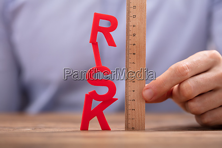 persons hand holding wooden ruler and