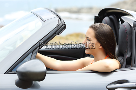 tourist driving a convertible car on