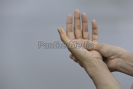 woman holding her hand pain in