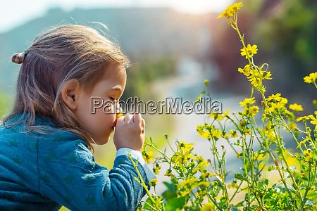 little boy enjoying flowers aroma