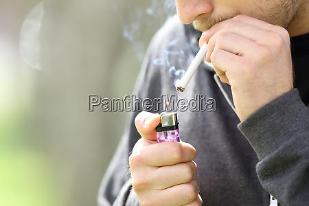 teen hands lighting a cigarette to
