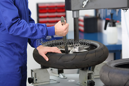 motorbike mechanic disassembling an old tire