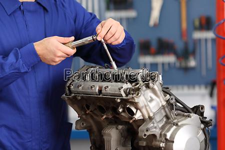 motorcycle mechanic repairing an engine