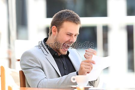 ejecutivo emocionado leyendo una carta en