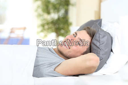 happy man resting on a bed