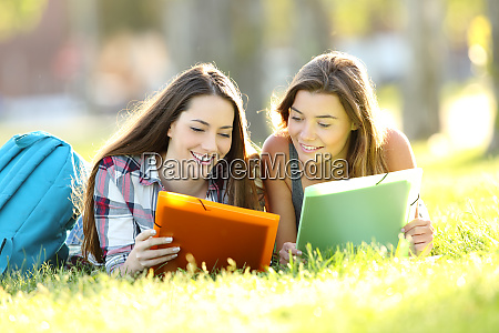 two students studying reading notes outdoors