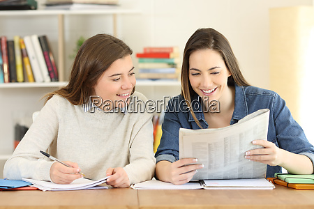 two happy students reading a newspaper