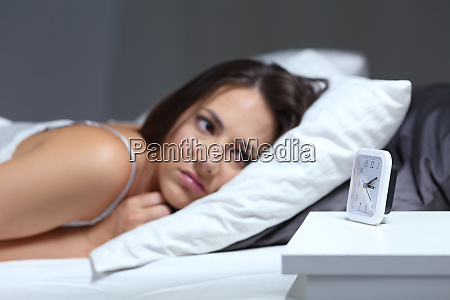 insomniac woman looking at alarm clock