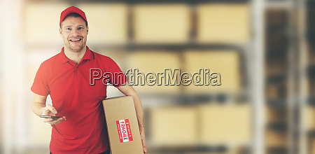 delivery man standing in warehouse holding