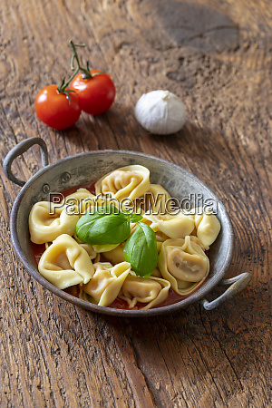 tortellini on wood with tomato sauce
