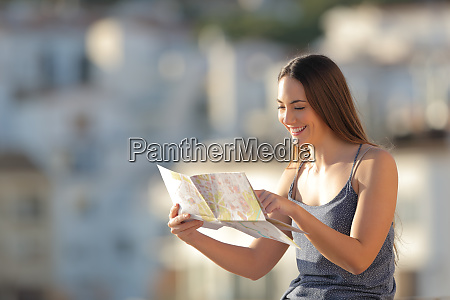 happy tourist checking map on vacation
