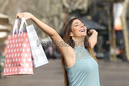 happy shopper holding shopping bags in