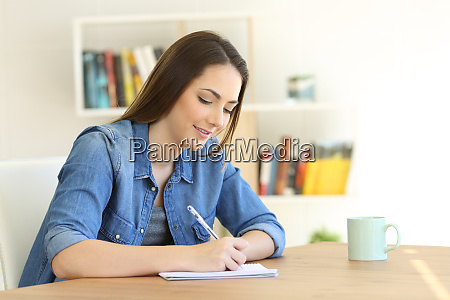 girl writing in a notebook at